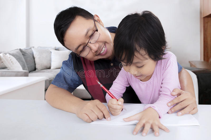 Fadern vägleder hennes dotter som gör läxa arkivbild