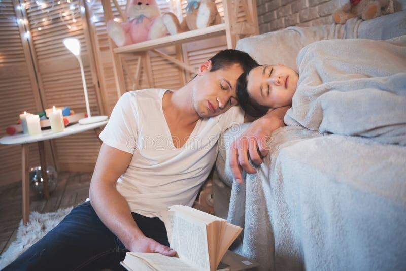 Fadern var den läs- sagaboken till hans son på natten hemma Både mannen och pojken sover royaltyfria foton