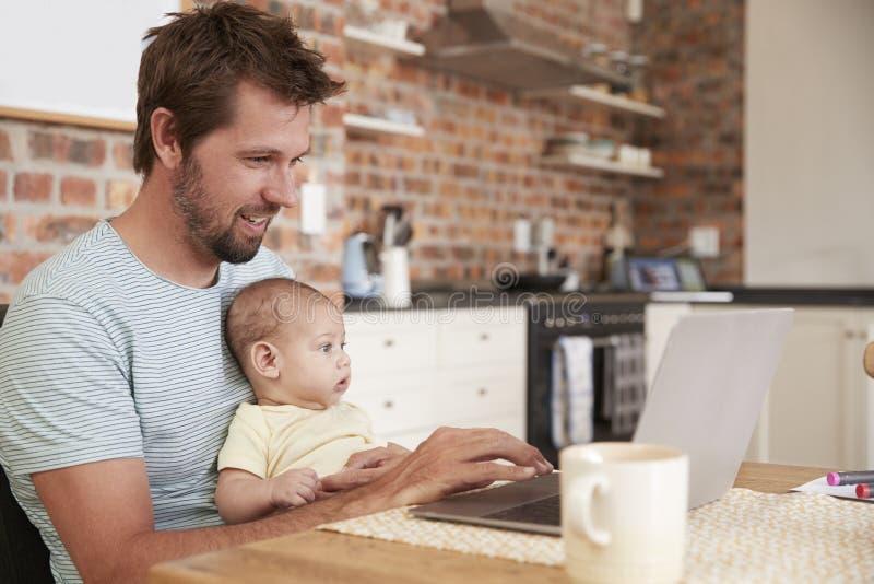 Fadern Working From Home på bärbara datorn med behandla som ett barn sonen royaltyfria bilder