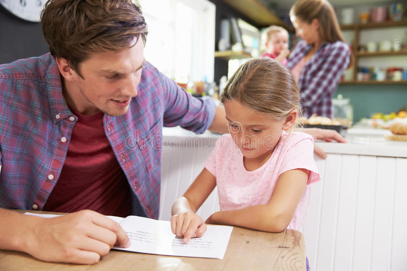 FaderReading Book With dotter på köksbordet royaltyfri foto