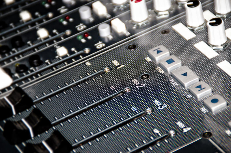 Faders and buttons on a mixing board. Midi faders and play, stop, record, fast forward, rewind on a mixing board/console royalty free stock photography