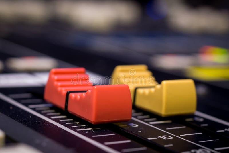 Faders vermelhos e amarelos do console de mistura audio profissional foto de stock royalty free