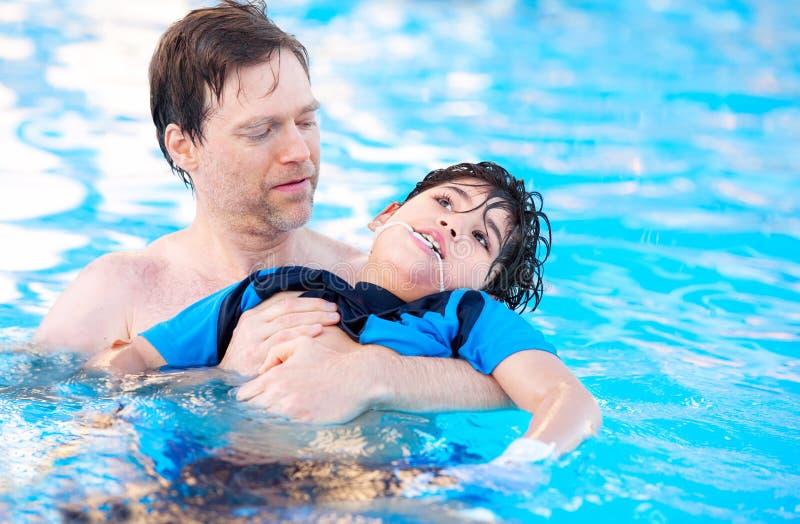 Fadersimning i pöl med det rörelsehindrade barnet royaltyfri foto