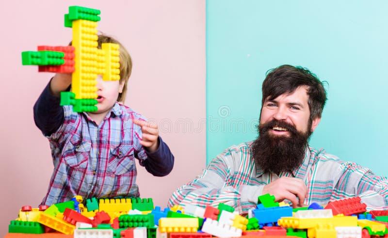 Fadersonen skapar konstruktioner Fader- och pojkelek tillsammans Farsa och unge att bygga plast- kvarter Faderledarevisning arkivbild