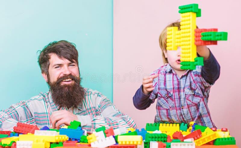Fadersonen skapar konstruktioner Fader- och pojkelek tillsammans Farsa och unge att bygga plast- kvarter Faderledarevisning royaltyfri fotografi