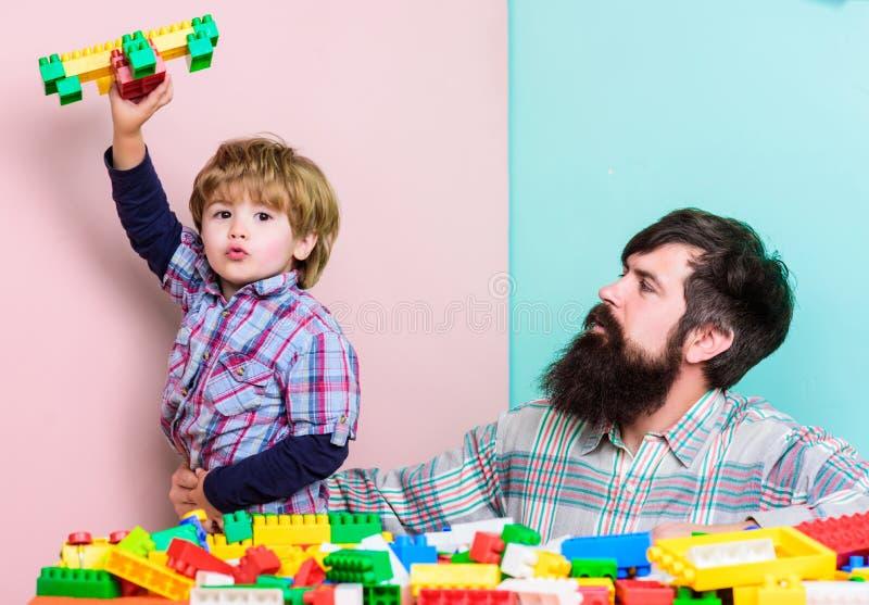Fadersonlek Fadern och sonen skapar konstruktioner Sk?ggig man- och sonlek tillsammans Varje farsa och son måste göra arkivfoto