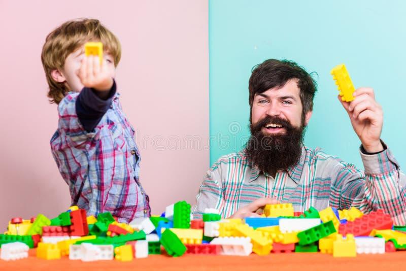 Fadersonlek Fadern och sonen skapar konstruktioner Sk?ggig man- och sonlek tillsammans Varje farsa och son m?ste g?ra royaltyfri foto