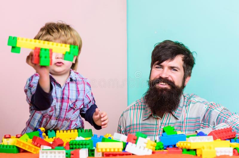 Fadersonlek Fadersonen skapar konstruktioner Fader- och pojkelek tillsammans Farsa och unge att bygga plast- kvarter fader arkivbilder