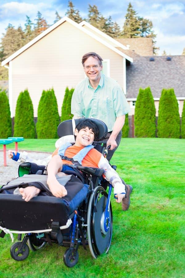 Faderspring med den rörelsehindrade sonen i rullstol fotografering för bildbyråer