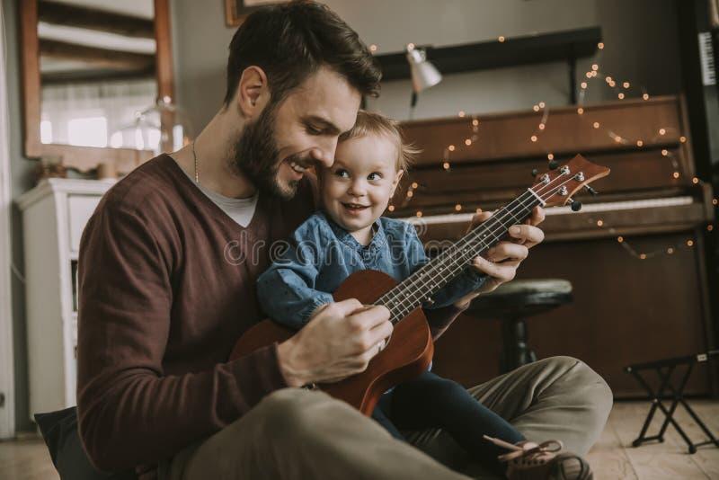 Faderundervisningdotter som hemma spelar gitarren fotografering för bildbyråer