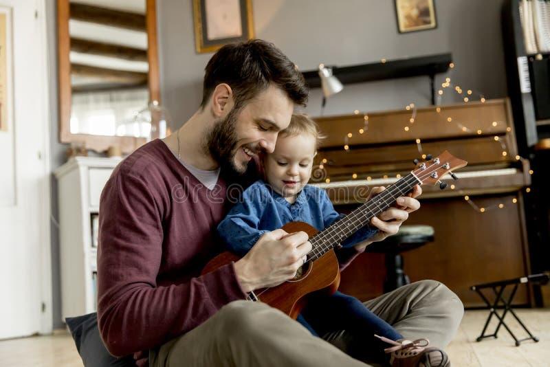 Faderundervisningdotter som hemma spelar gitarren royaltyfri foto