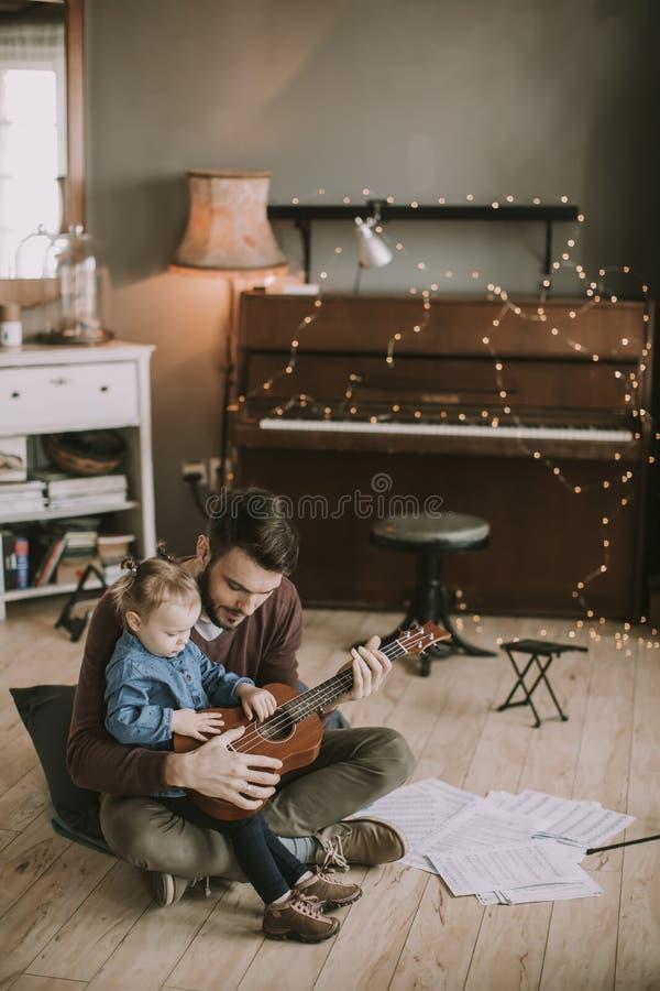 Faderundervisningdotter som hemma spelar gitarren royaltyfria foton