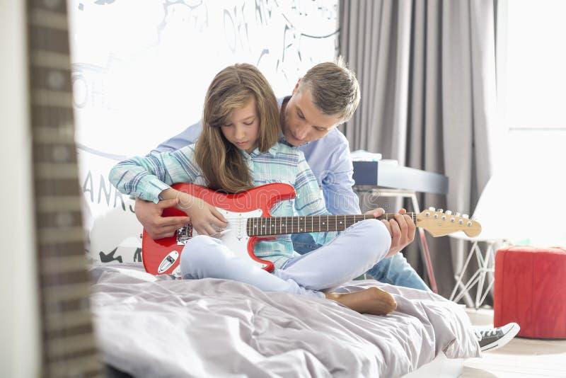 Faderundervisningdotter som hemma spelar gitarren arkivbilder