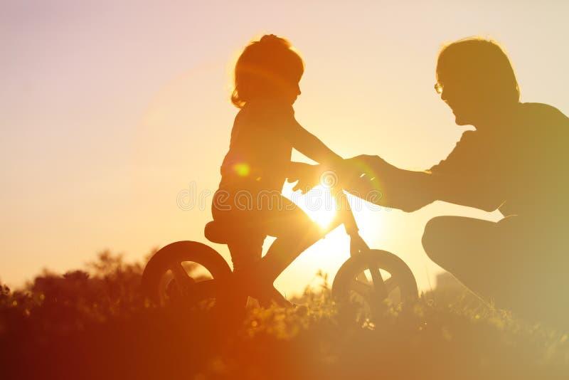Faderundervisningdotter som rider cykeln på solnedgången royaltyfri foto