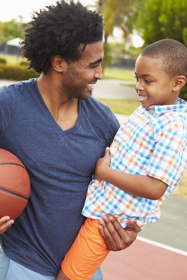 FaderWith Son Playing basket parkerar in tillsammans fotografering för bildbyråer