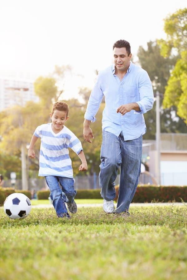 FaderWith Son Playing fotboll parkerar in tillsammans arkivbild