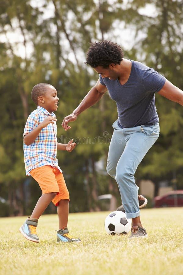 FaderWith Son Playing fotboll parkerar in tillsammans arkivfoton