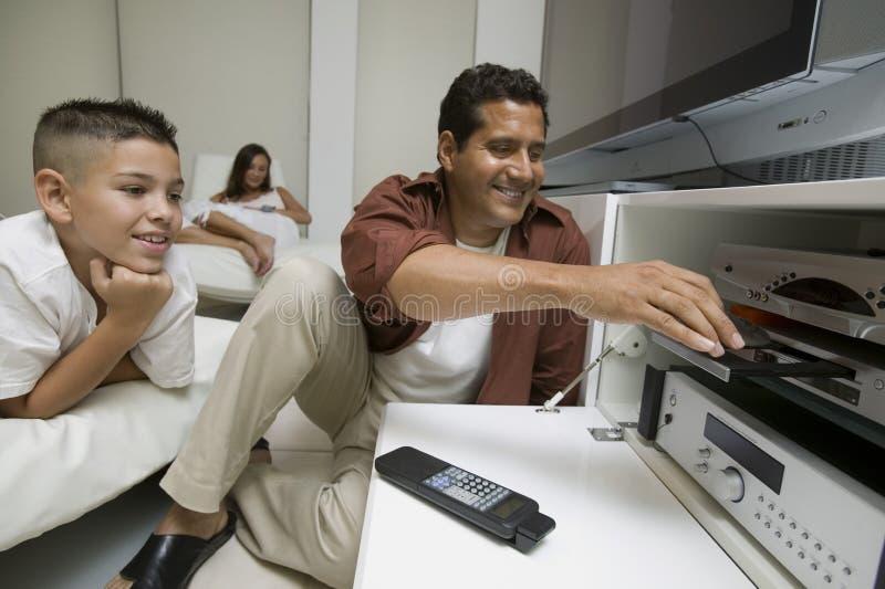 FaderWith Son Putting diskett i DVD-spelare hemma fotografering för bildbyråer