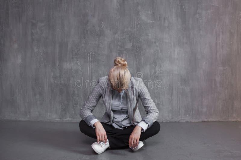 Fadiga, neutralização profissional Jovem mulher no terno de negócio que senta-se na pose de Lotus, cabeça para baixo fotografia de stock