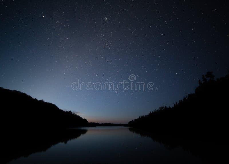 Fading gwiazdy w wczesnego poranku niebie odbijają w spokojnym jeziorze obraz royalty free
