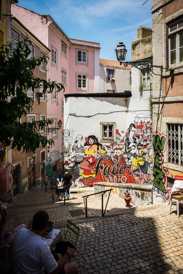Fado graffiti w alei w Lisbon Portugalia z dżentelmenu obsiadaniem w cieniu zdjęcie stock