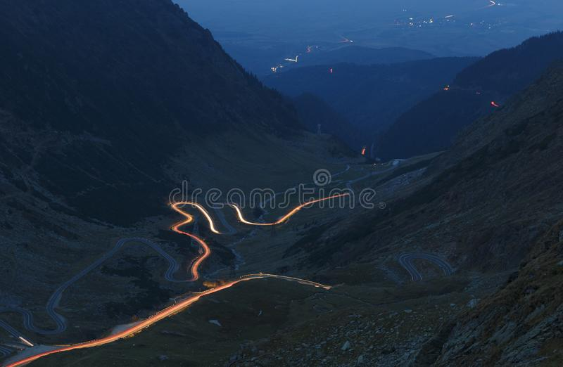 Fagaras mountains in Romania in the summer evening with Transfagarasan winding road with lights stock photo