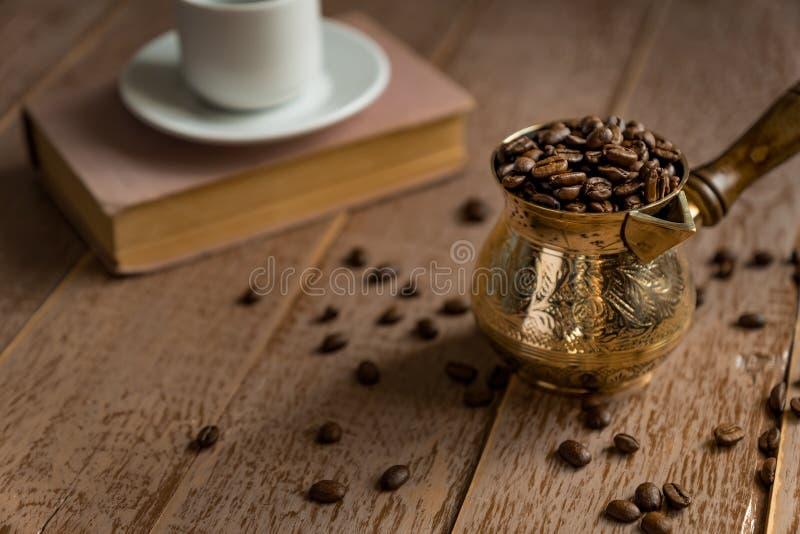 Fagioli arrostiti freschi del coffe in mistero e tazza turchi tradizionali della caffettiera del cezve sulla tavola di legno immagini stock