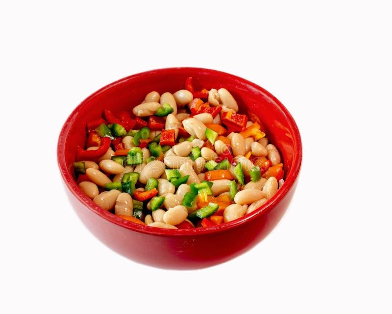 Fagioli bianchi e peperoni dolci in ciotola rossa su bianco immagine stock