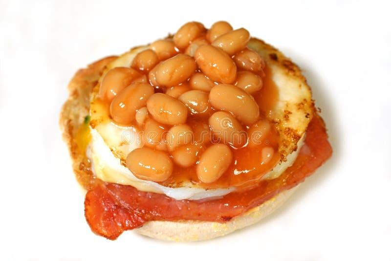 Fagioli cotti su una focaccina della pancetta affumicata e dell'uovo fotografie stock libere da diritti