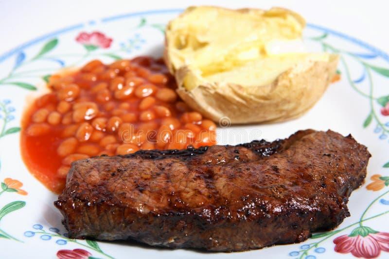 Fagioli e patata cotti arrostiti col barbecue della bistecca di lombata fotografia stock libera da diritti