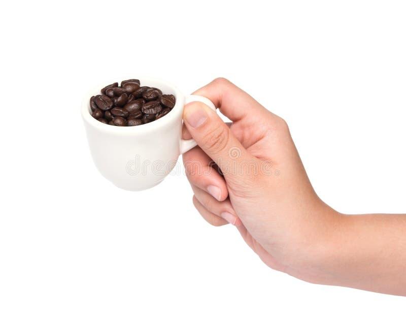 Fagioli femminili della tazza di caffè della tenuta della mano isolati su backgroun bianco immagini stock