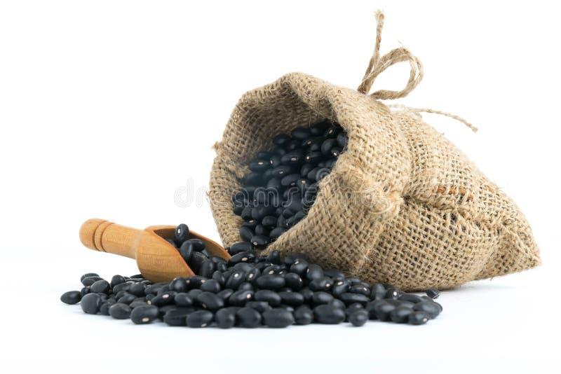 fagioli neri in sacco della tela su bianco immagini stock