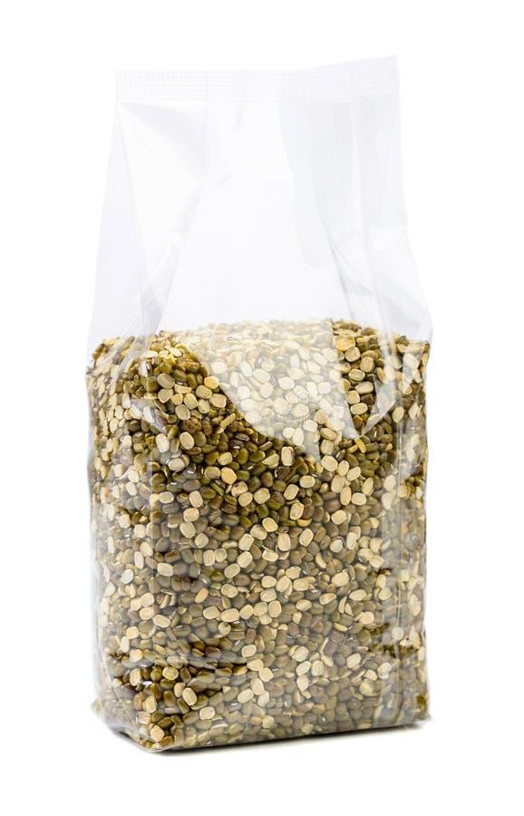 Fagioli verdi o lenticchie in un imballaggio trasparente isolato su bianco fotografie stock