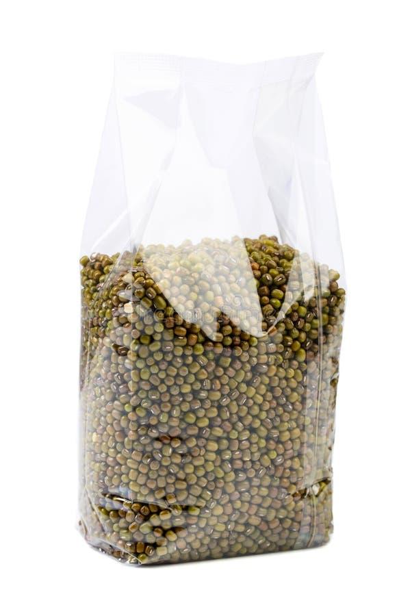 Fagioli verdi o lenticchie in un imballaggio trasparente isolato su bianco immagini stock libere da diritti