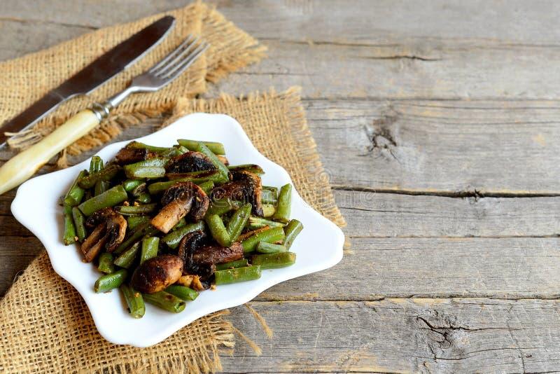 Fagiolini fritti deliziosi con i funghi e le spezie su un piatto e su vecchio fondo di legno con lo spazio della copia per testo fotografie stock libere da diritti