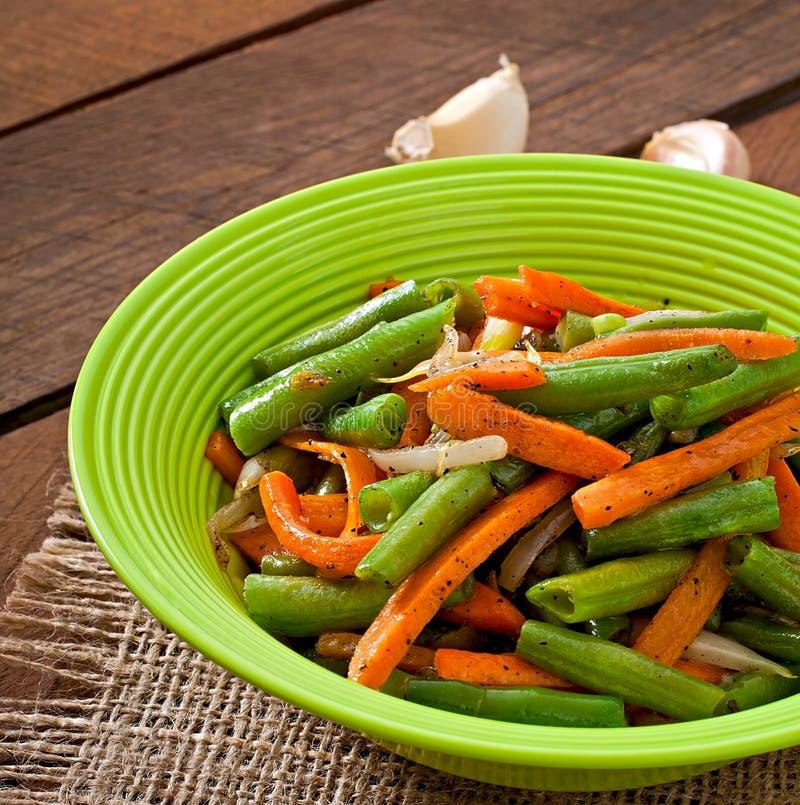 Fagiolini sauteed con le carote, la cipolla e l'aglio fotografie stock