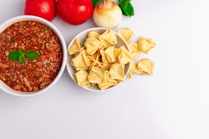 Fagottini Tortellini pasta with Bolognese also know as Bolognesa or Bolonhesa sauce in a white bowl isolated in white background stock image