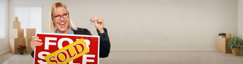 Fahne der erwachsenen Frau innerhalb des Raumes mit den Kästen, die Haus-Schlüssel halten stockfoto