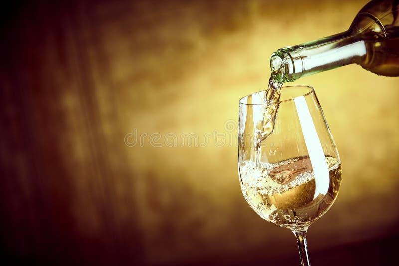 Fahne, die ein Glas Weißwein von einer Flasche ofPouring ist lizenzfreies stockfoto
