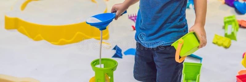 FAHNE Junge, der mit Sand in der Vorschule spielt Die Entwicklung des feinen Bewegungskonzeptes Langes Format des Kreativitäts-Sp stockbilder
