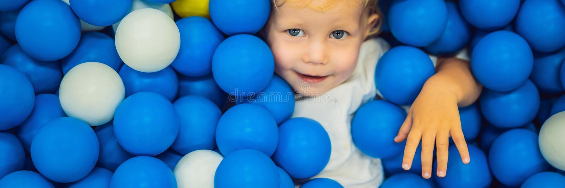FAHNE, LANGES FORMAT Kind, das in der Ballgrube spielt Bunte Spielwaren f?r Kinder Kindergarten oder Vorschule- Spielraum Kleinki stockfotografie