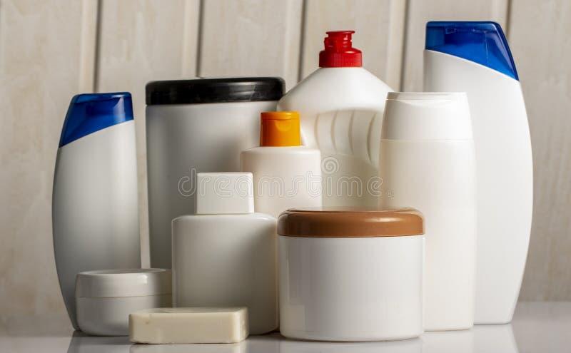 Fahnen-Haar und weiße Flaschen der Körperpflegekosmetik auf selektivem Fokus des weißen Hintergrund Kopienraumes lizenzfreie stockfotos