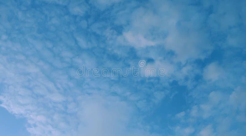 Fahnen-Kumuluswolken des Sonnenuntergangs mit dem unscharfen defocusing Hintergrund des blauen Himmels des Sonnenuntergangs stockfoto