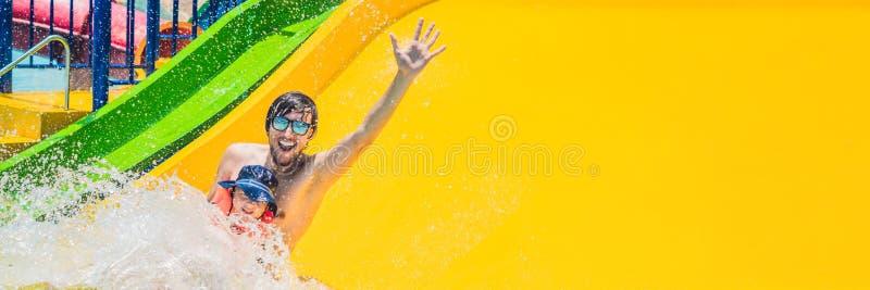 FAHNEN-Vater und -sohn auf Wasserrutschen im Wasser parken langes Format lizenzfreies stockfoto