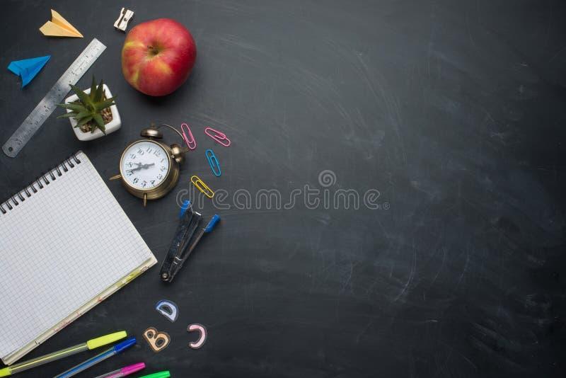 Fahnenkonzept zurück zu Schulwecker, Bleistift Apple-Notizbuch-Briefpapier auf Tafelhintergrund Entwurfs-Kopien-Raum accessorie lizenzfreie stockfotos