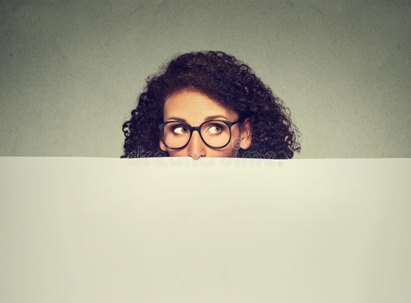 Fahnenzeichenfrau, die über Rand der leeren leeren Anschlagtafel mit Kopienraum für Text späht stockfotos
