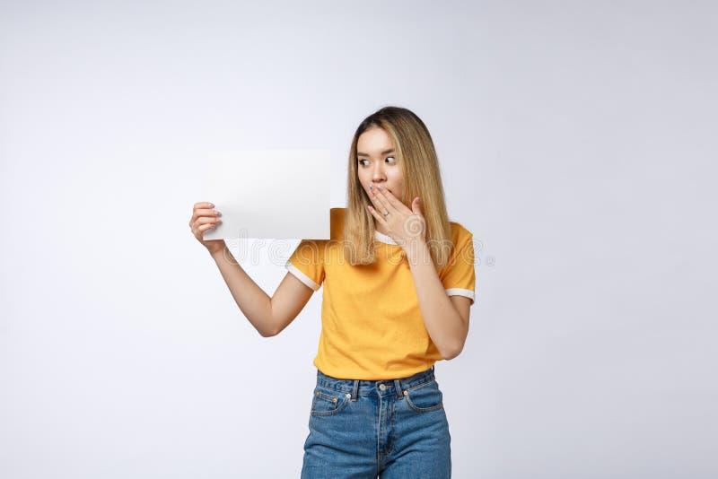Fahnenzeichenfrau, die über Rand der unbelegten leeren Papieranschlagtafel mit Exemplarplatz für Text späht Schöner asiatischer K stockbild