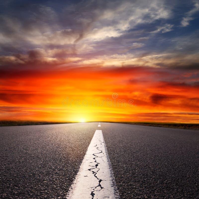 Fahren auf eine leere Asphaltstraße bei Sonnenuntergang stockbilder