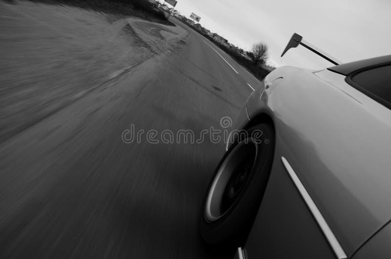 Fahren an der hohen Geschwindigkeit hinunter eine Landstraße stockbild