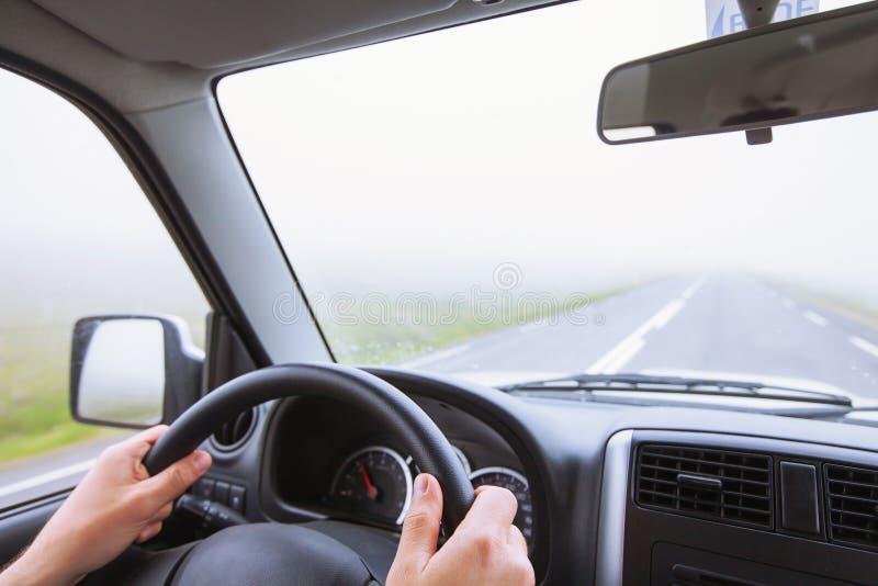 Fahren des Autos im Nebel, ungünstige Wetterbedingungen, Straße stockfotografie